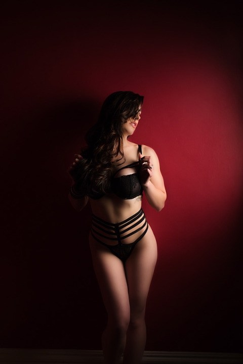 dramatic light boudoir photo of girl stand on wall in black bra & panty set by Asos. Photo by Pittsburgh boudoir Photographer Pics By Chicks Photography