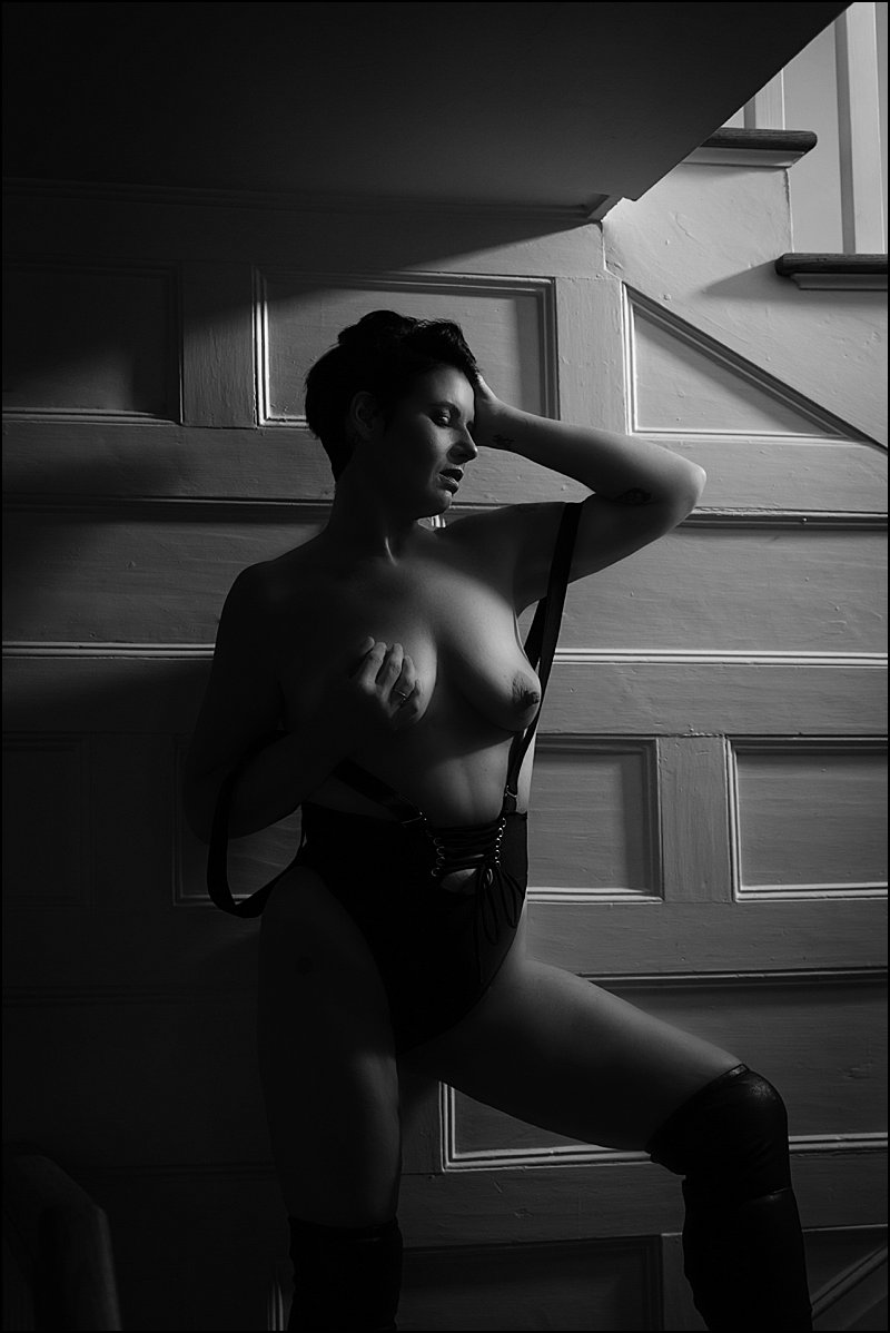 boudoir sexy photos by maura chick of woman in black suspender lingerie on steps at boudoir studio in pittsburgh